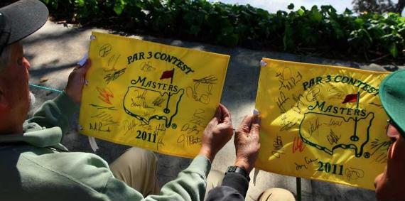 Dos aficionados comparan los autógrafos que han conseguido en el concurso de pares 3 del Masters